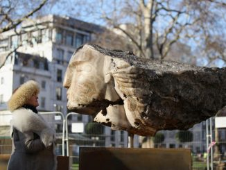 Giant Stone Heads Created By British Sculptor Emily Young Are Winched Into Berkeley Square