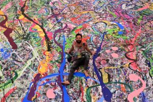 Sacha Jafri working on his record-breaking painting The Journey of Humanity.